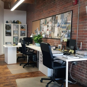 computer desk and chairs against a brick wall